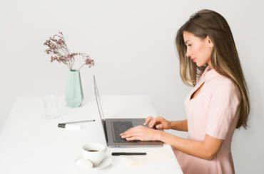 woman-in-pink-dress-using-laptop-computer-1586973